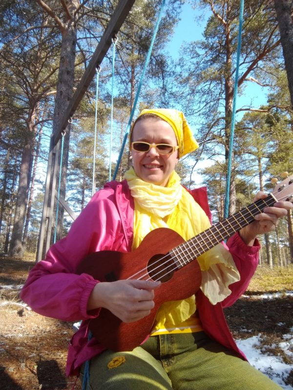Mari Liukkonen istuu auringonpaisteessa huivi päässä ja soittaa ukulelea.
