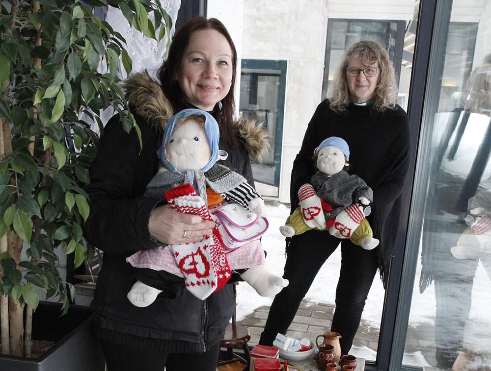 Riikka Ikonen ja Erja Haho pitävät käsissään nukkeja näyttelytilassa.