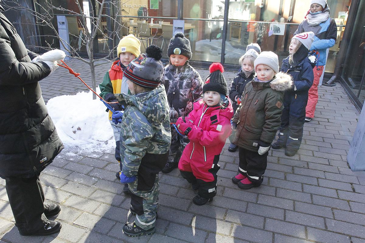 Lapset seisovat ulkona toppavaatteissa parijonossa.