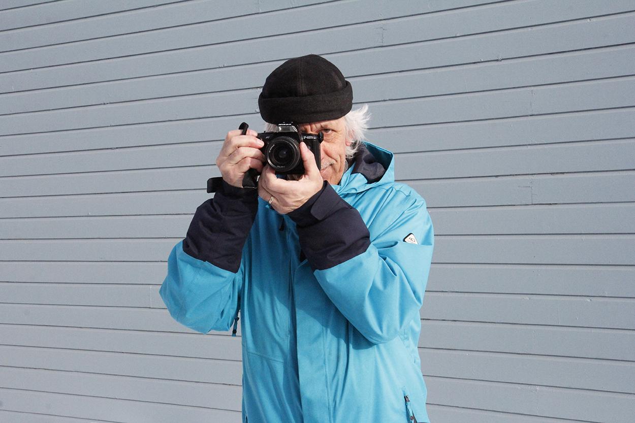 Unto Liimataisella on käsissään kamera, jolla hän tähtää kuvan ottajaa.