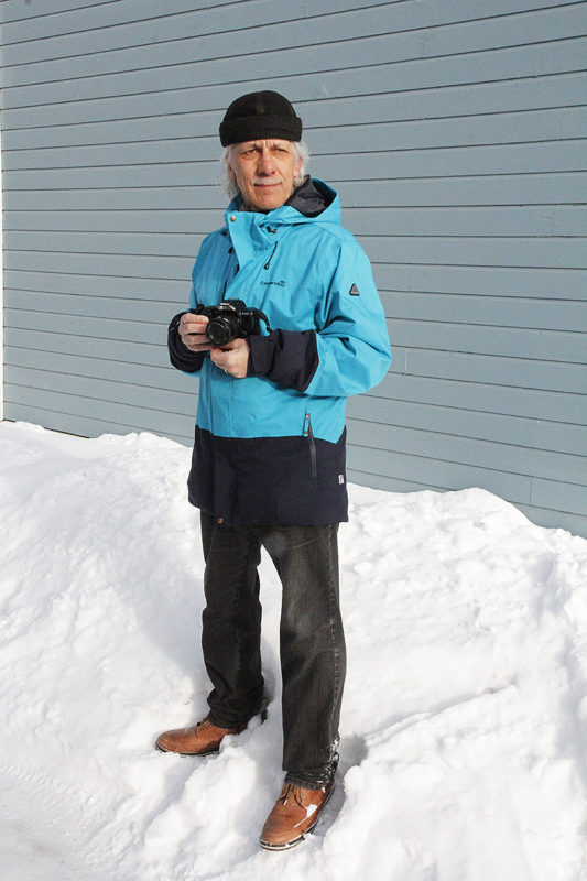 Unto Liimatainen seisoo kamera käsissään ja katsoo viistosti oikealle.