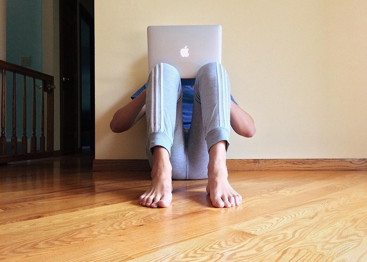 Poika istuu lattialla ja hänen kasvojensa edessä on kannettava tietokone.