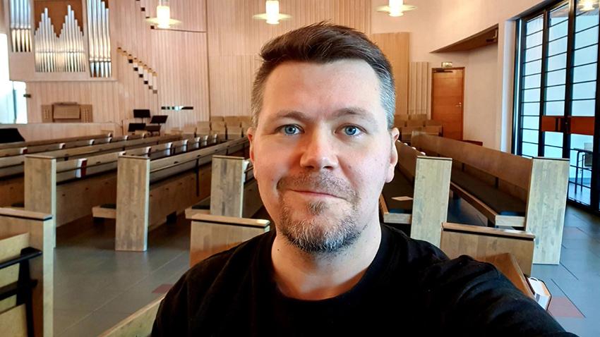 Tuukka Myllymäki seisoo kirkossa, katsoo kameraan ja hymyilee.