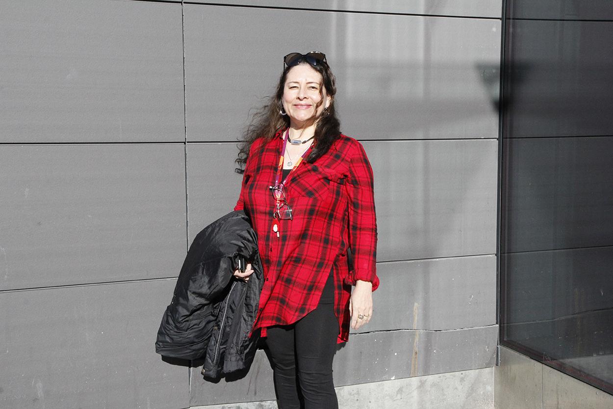 Luz Peltoniemi seisoo seinän edessä auringonpaisteessa toisessa kädessään takki.