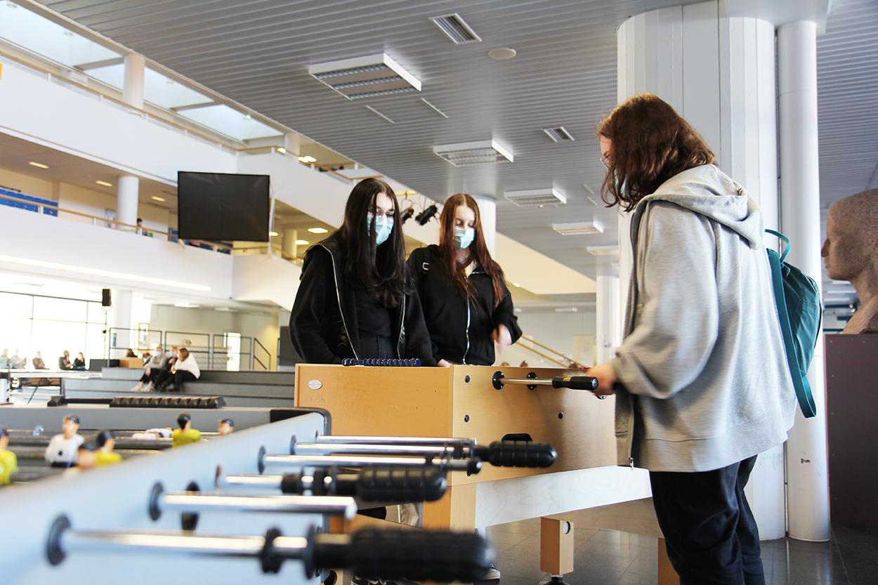 Tytöt pelaavat peliä koulun aulassa.