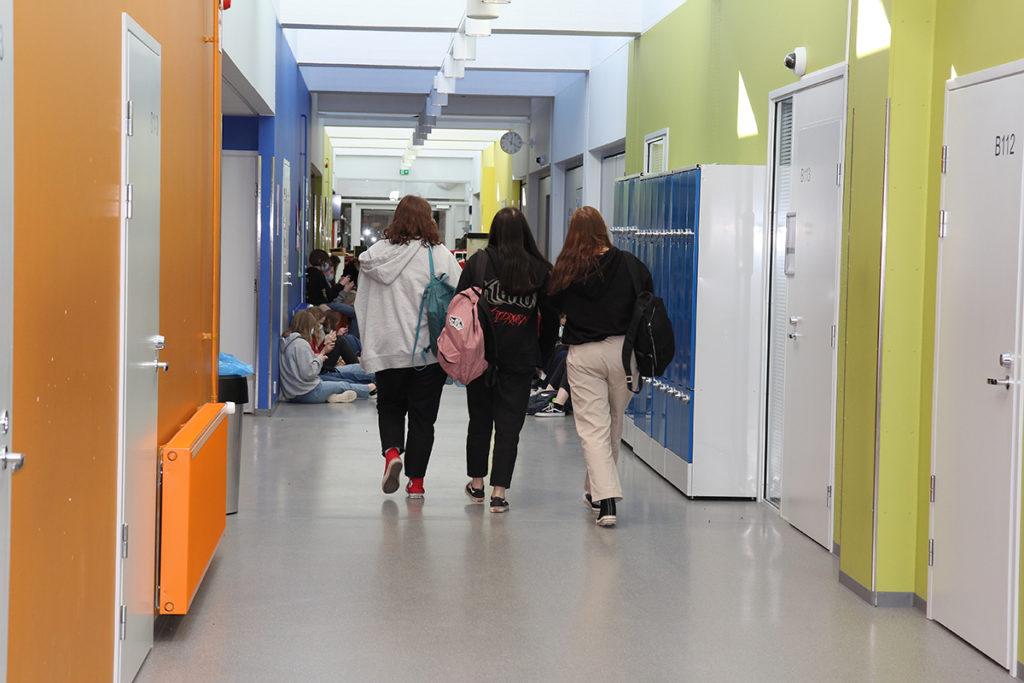 Kolme nuorta kävelee koulun käytävää pitkin.