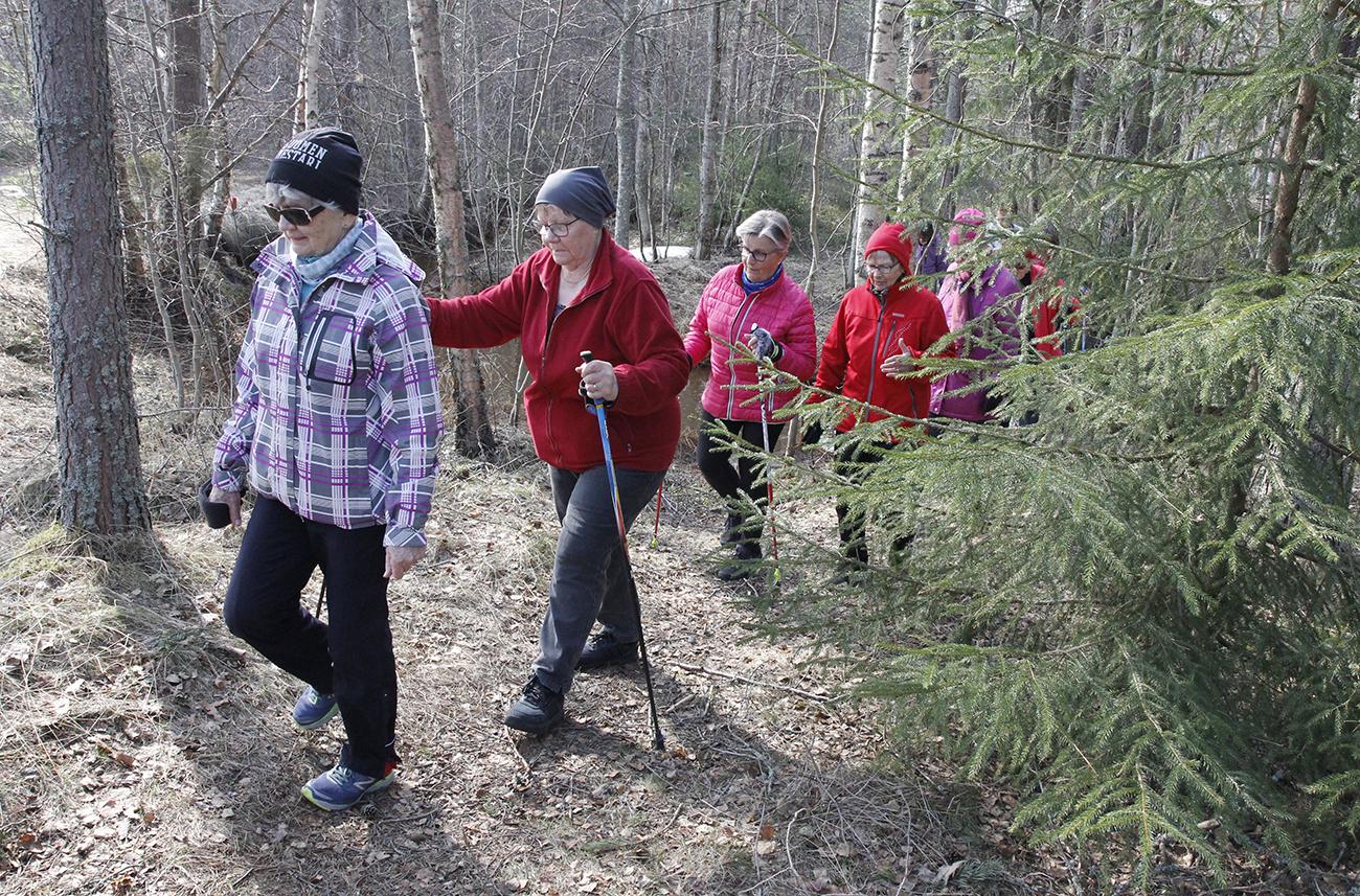 Neljä naista kävelee metsäpolulla peräkkäin.