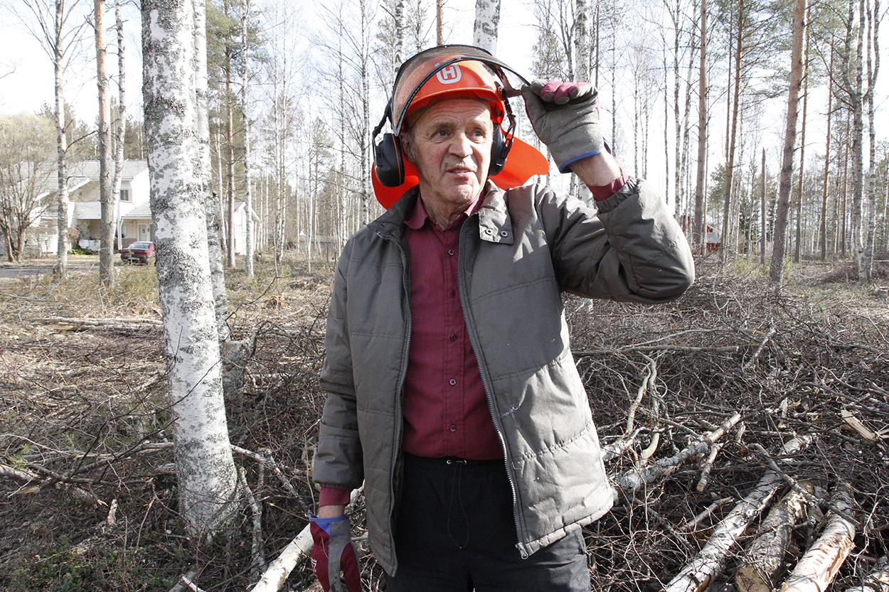 Matti Nikkilä seisoo metsikössä kypärä päässä ja kohottaa suojavisiiriä.