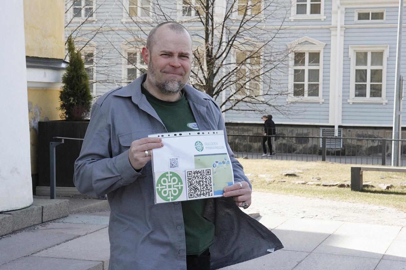 Jarmo Korhonen seisoo tuomiokirkon edessä ja pitää käsissään pyhiinvaellusreitistä kertovaa materiaalia.