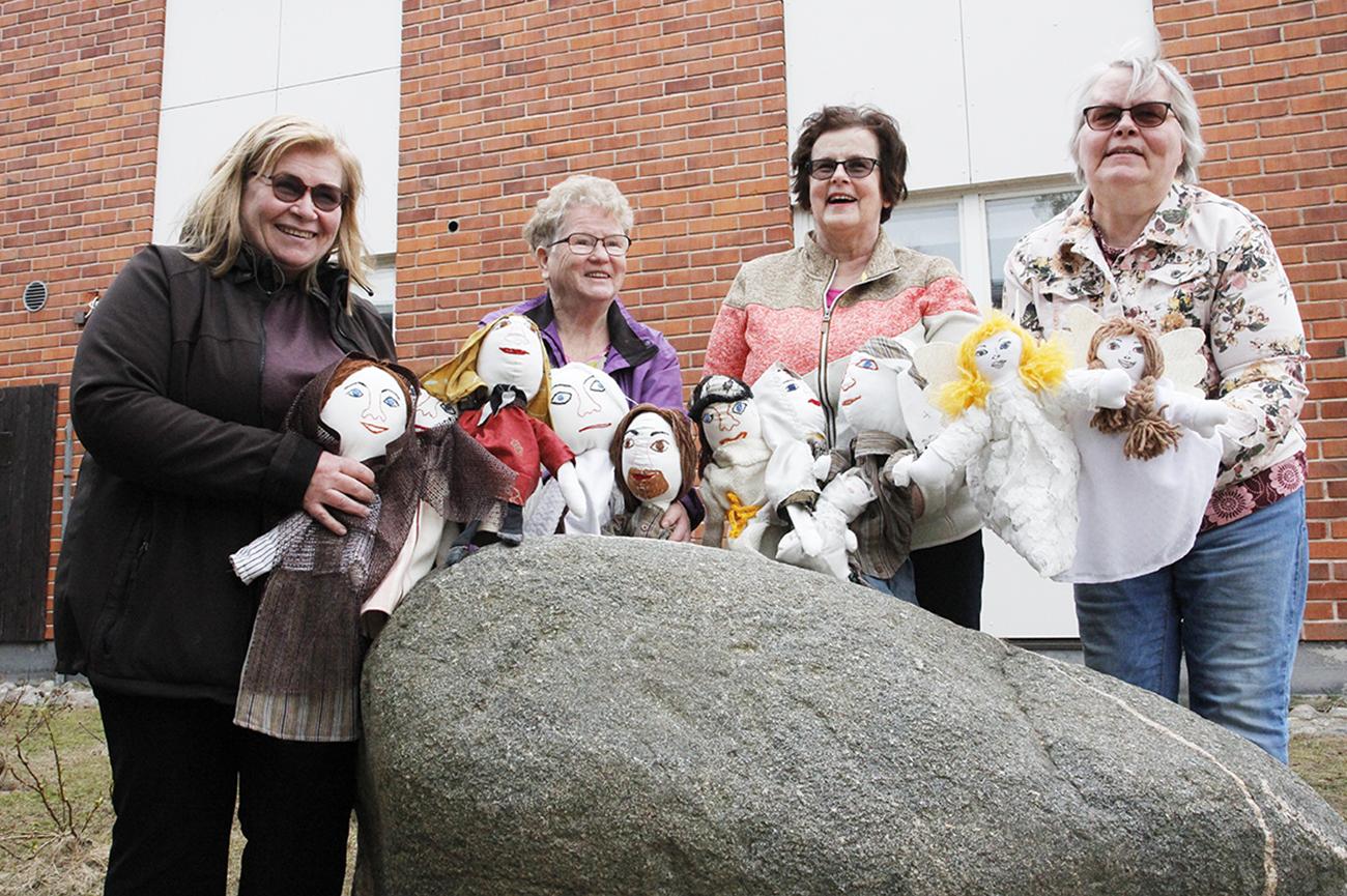 Arja Paavola, Taimi Soini, Pirjo Lahtimaa ja Tuovi Kyrö seisovat Lumojen seurakuntatalon edessä ja esittelevät valmiita nukkeja.