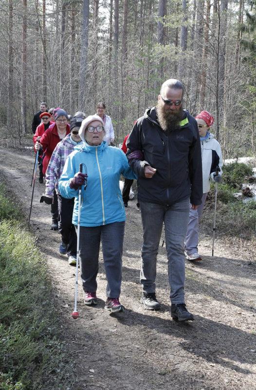 Raili Haapala ja Kimmo Sorvoja kävelevät metsäpolkua pitkin, takana tulee joukko muita kävelijöitä.