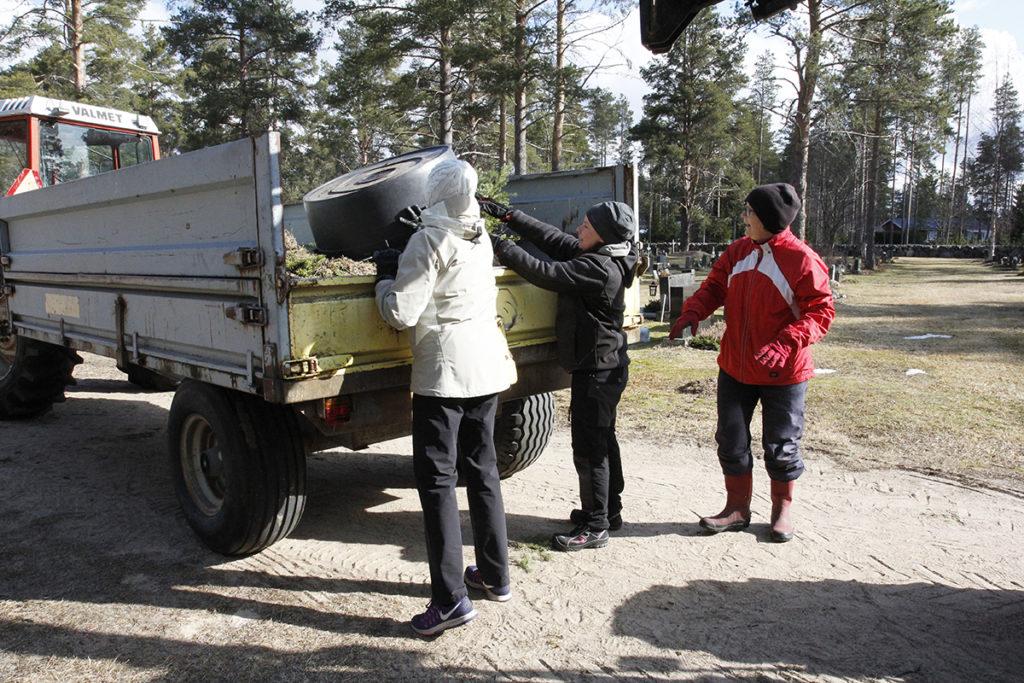 Pirjo Junkkonen, Maili Muuttola-Junkkonen ja Tarja Moilanen tyhjentävät astian traktorin peräkärryyn.