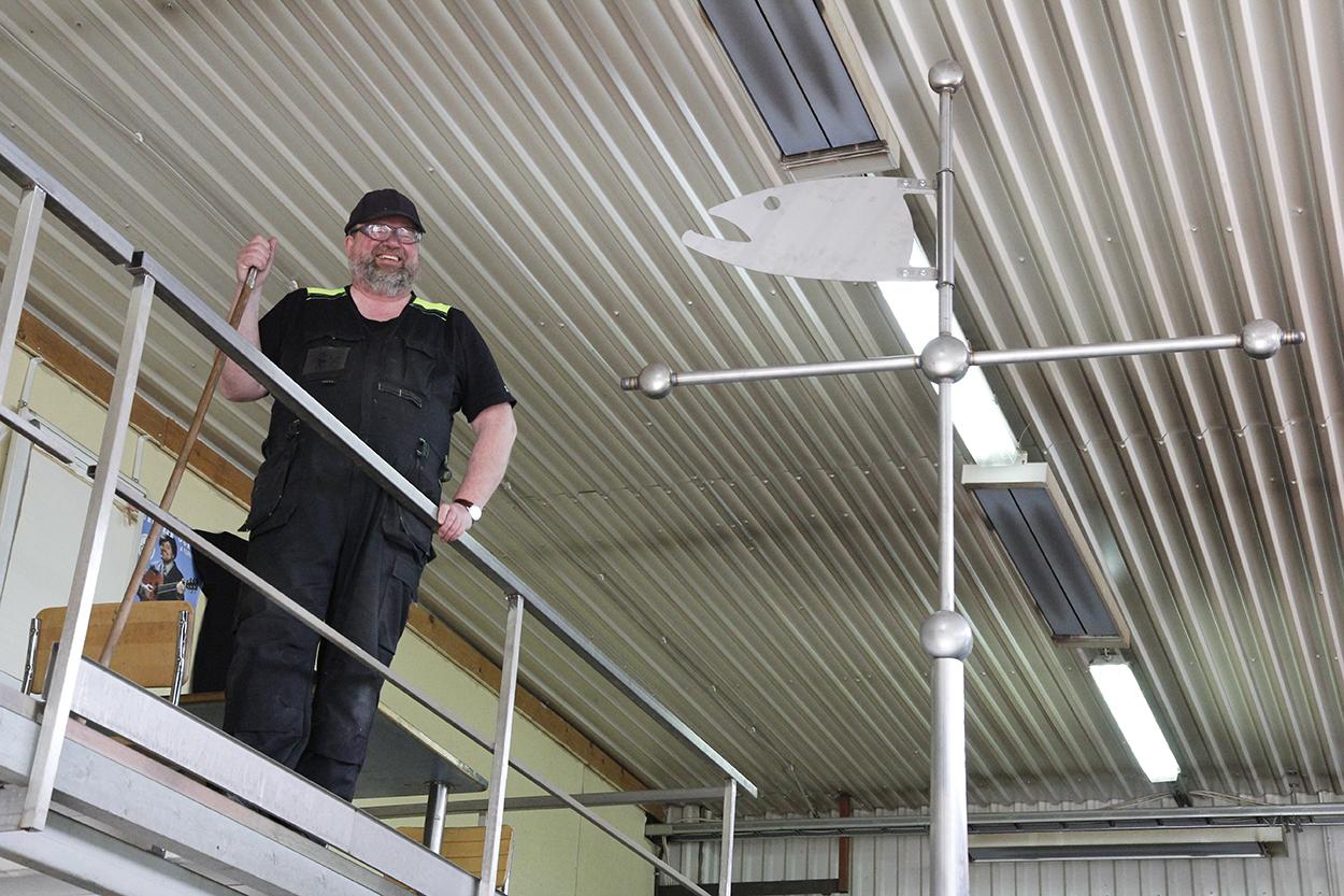 Mikko Jurvelin seisoo ylhäällä tason päällä vieressä viiri, josta näkyy sen päässä oleva risti ja lohikoriste.