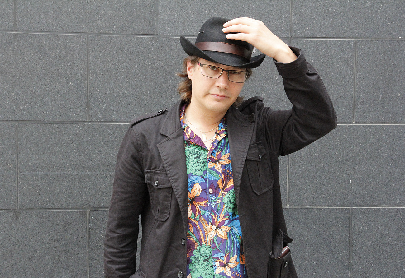Juha Korhonen pitää yhdellä kädellä kiinni päässään olevasta hatusta ja katsoo kameraan.