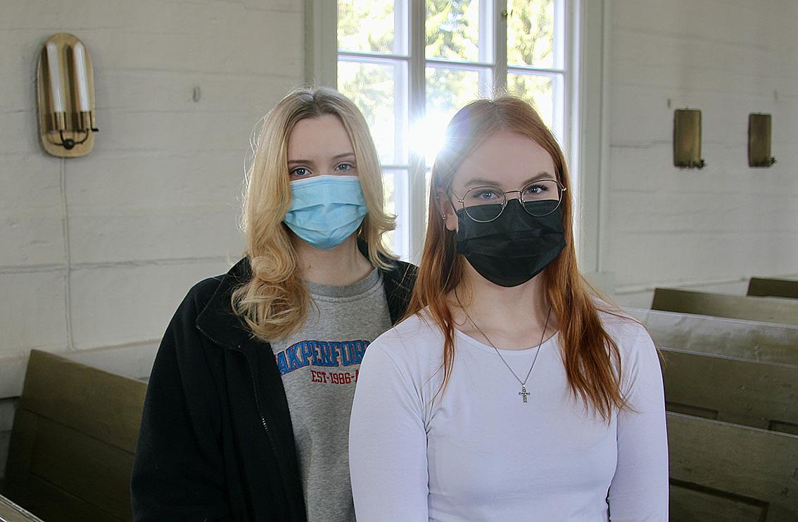 Kaksi nuorta naista maskit kasvoillaan seisoo kirkossa ja katsoo kameraan päin.