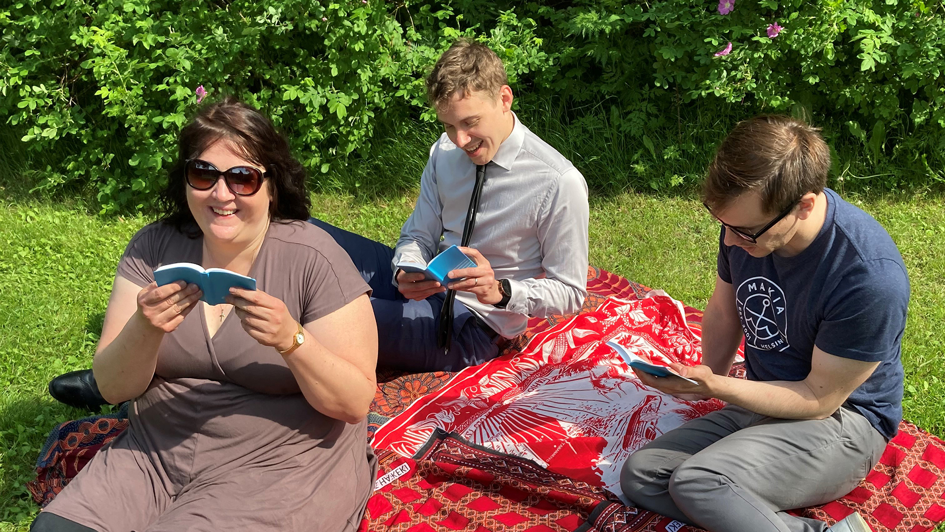 Kolme ihmistä istuu puistossa viltillä.