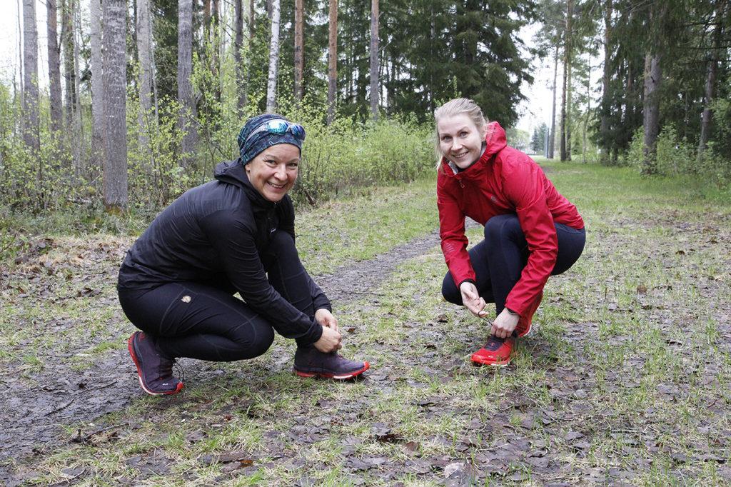 Naiset sitovat kengännauhojaan.