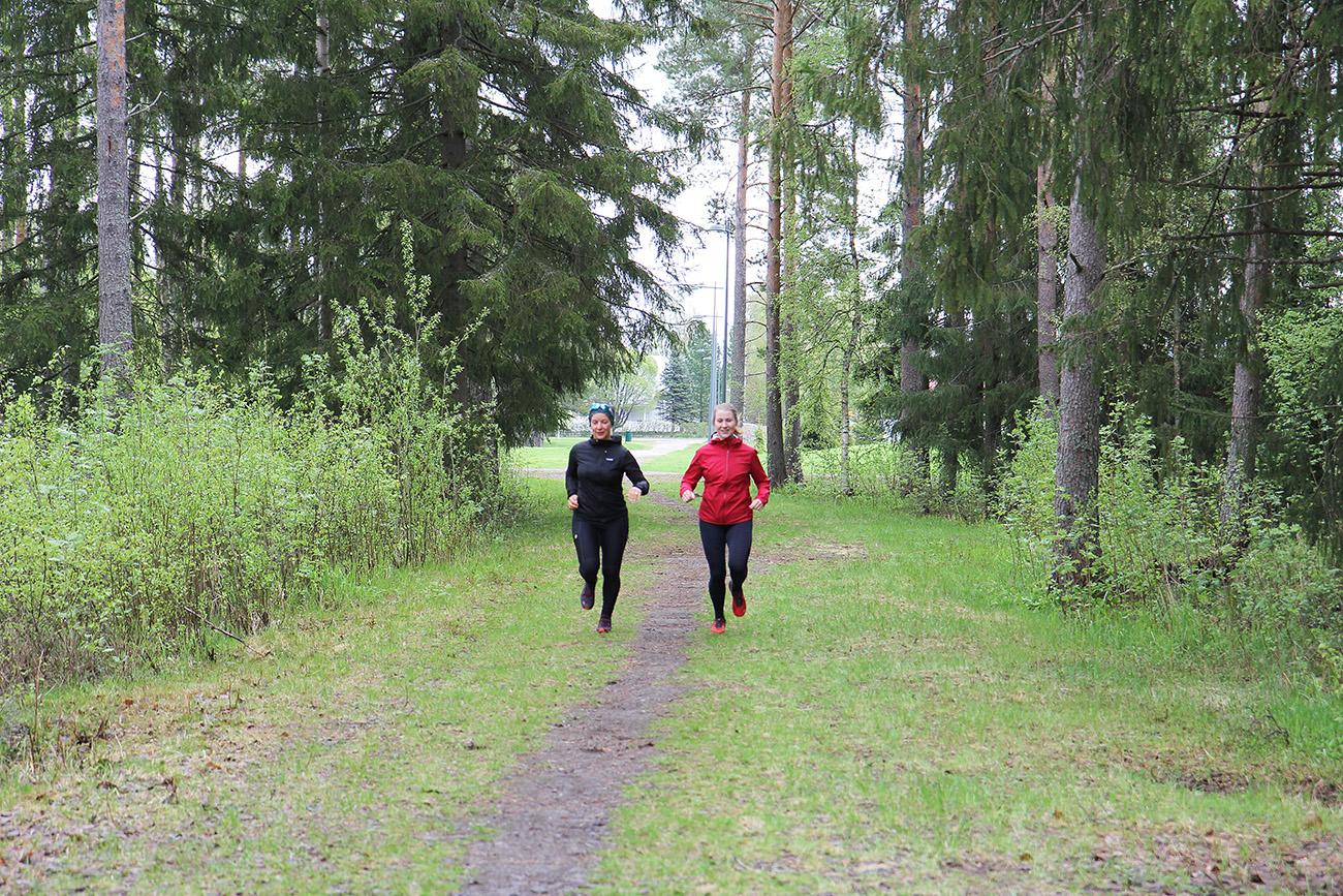 Naiset juoksevat metsässä.
