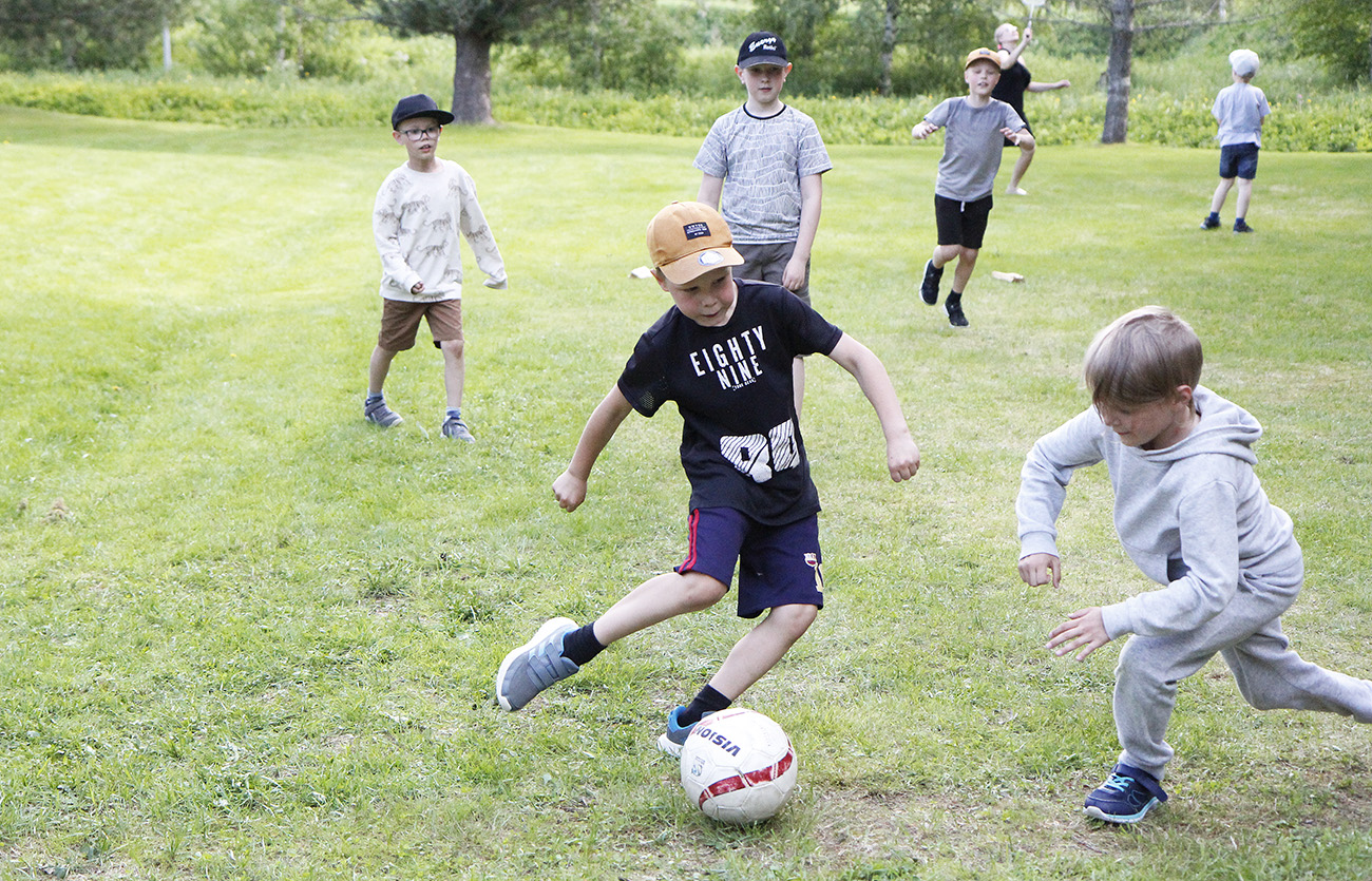 Poika on potkaisemassa palloa, muut pojat seuraavat ympärillä.