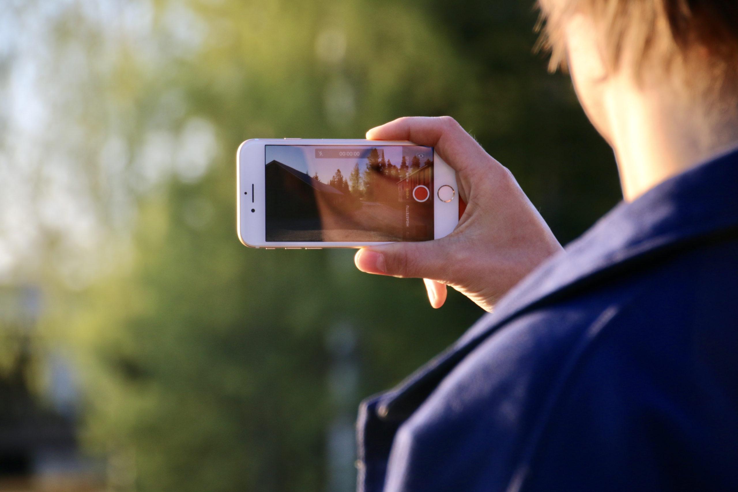 Selin kameraan oleva nuori mies pitää kädessään kännykkää, jolla hän ottaa kuvaa itsestään. Kännykkäkameran ruudulla näkyy hymyilevä suu.