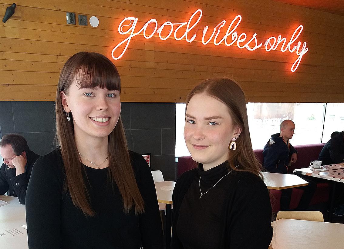 """Kaksi mustiin paitoihin pukeutunutta nuorta naista hymyilee kameralle. Taustalla näkyy pinkki neonvaloteksti, jossa lukee """"good vibes only""""."""