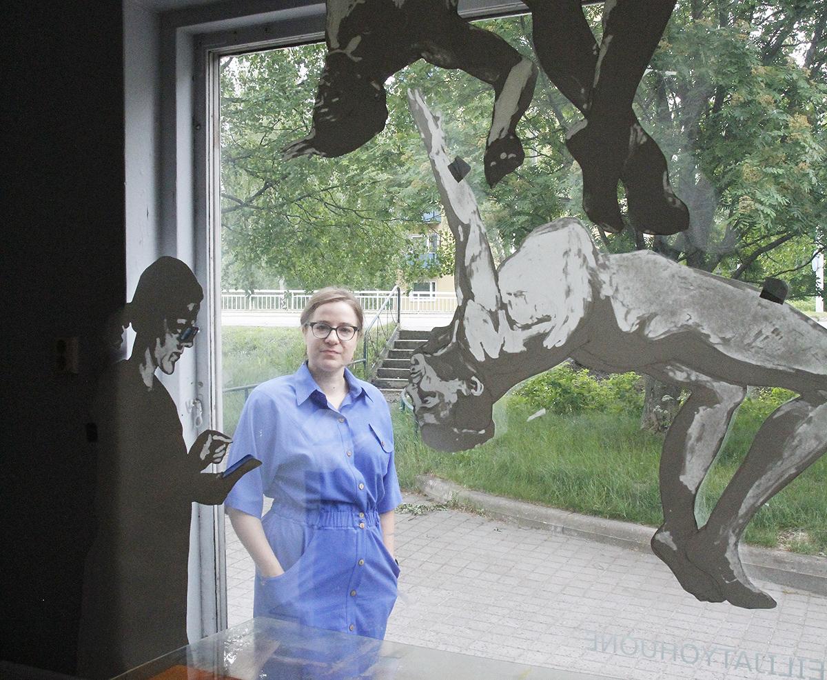 Anni Arffman katsoo kameraan ikkunalasin takaa. Ikkunassa on ihmishahmoja.