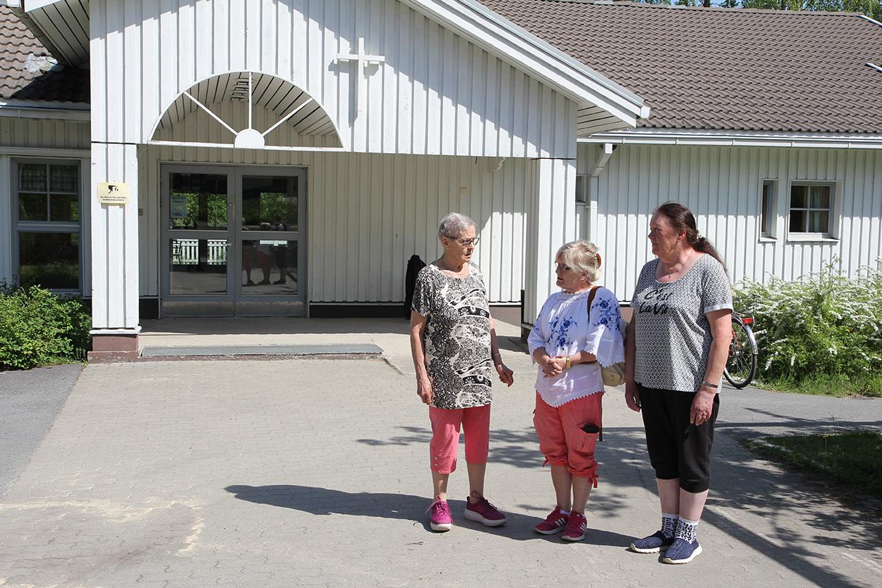 Senja Nikkinen, Aino Taipaleenmäki ja Arja Virta seisovat Martinniemen seurakuntakodin edessä.