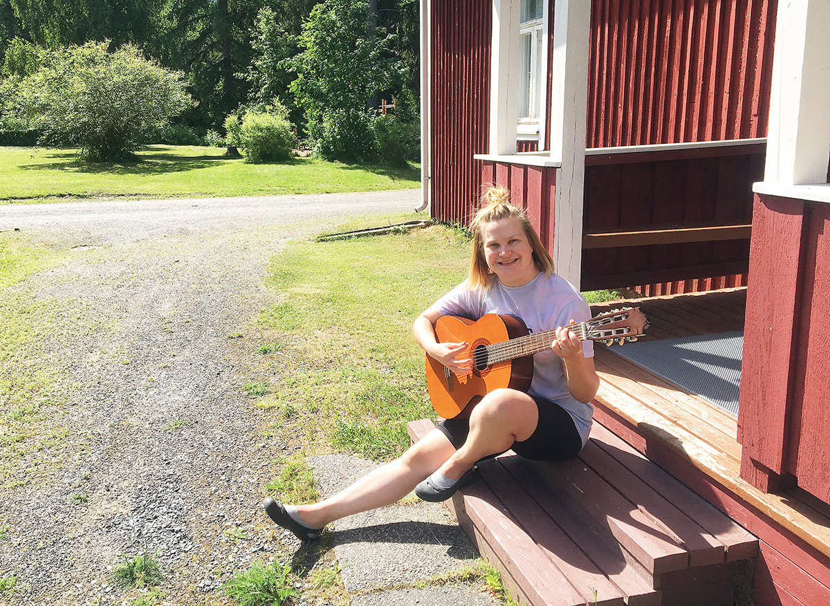 Laura Laine istuu kotiseutumuseon portailla kitara sylissään.