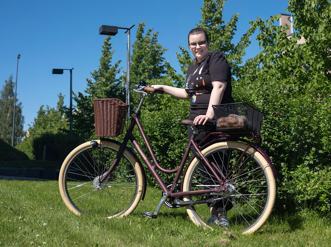 Nuori tummiin vaatteisiin pukeutunut nainen poseeraa mummomallisen polkupyörän kanssa nurmella.