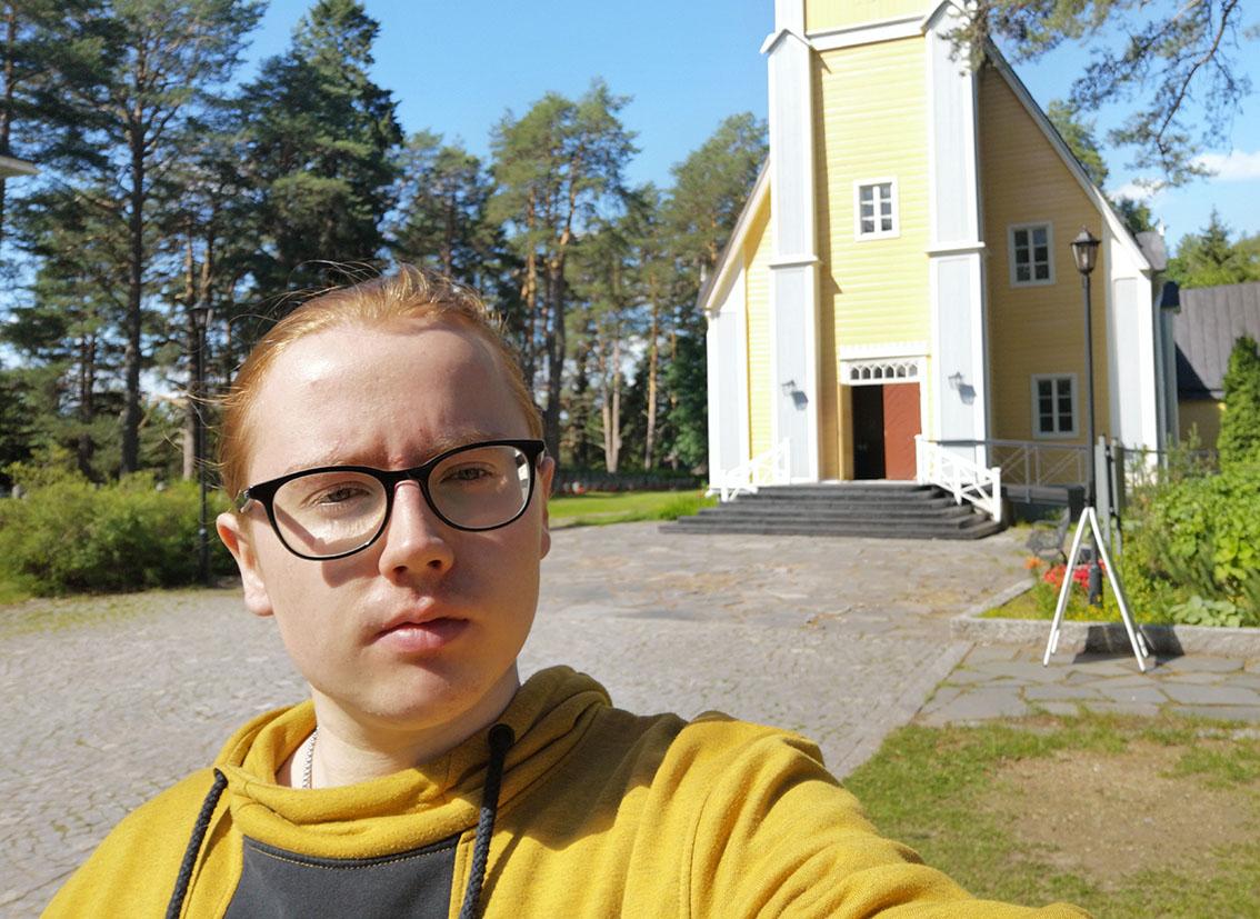 Nuori silmälasipäinen ja punatukkainen mies keltaisessa paidassa seisoo ja ottaa kuvan itsestään Muhoksen kirkon pihamaalla.
