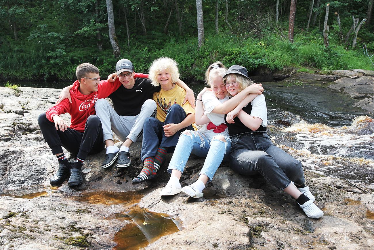 Nuoret istuvat joen rannalla ja halaavat toisiaan.