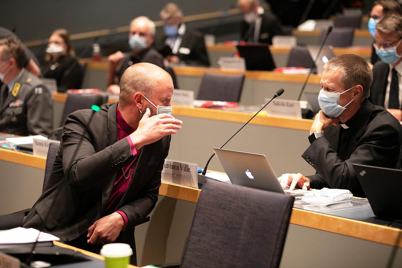 Helsingin piispa Teemu Laajasalo keskustelee kirkolliskokouksessa toisen edustajan kanssa.