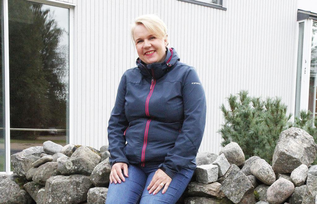 Marika Moilanen istuu seurakuntakeskuksen kiviaidalla.