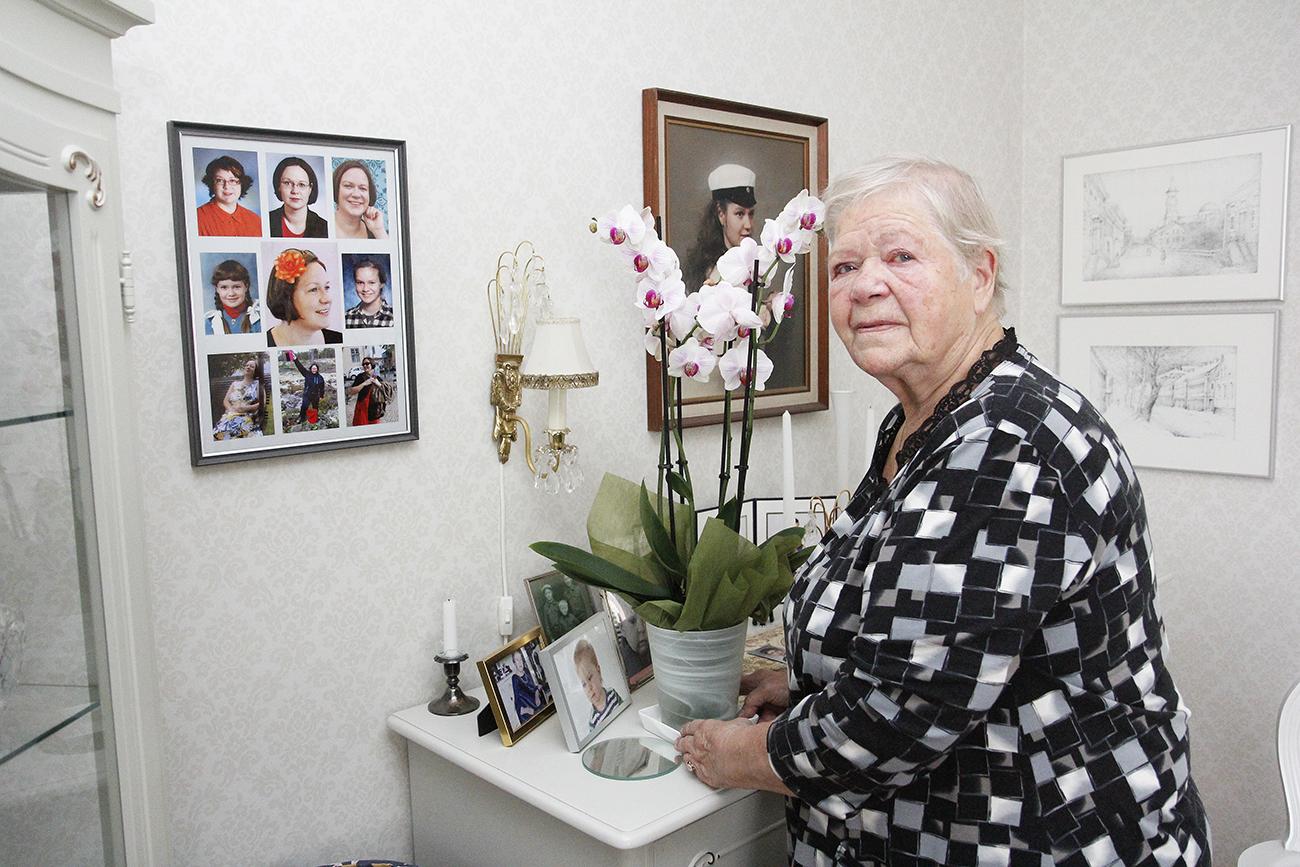 Maija Matikainen seisoo lipaston edessä. Seinällä on kuvia Heli-tyttärestä.
