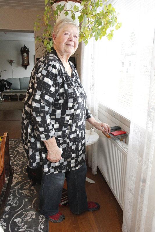 Maija Matikainen seisoo ikkunan ääressä ja hymyilee hieman.
