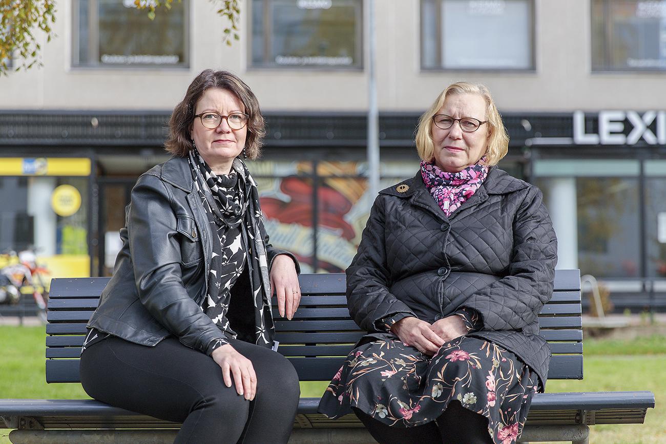 Sanna Lakso ja Ansku Saukkomaa istuvat puiston penkillä ja katsovat kameraan.