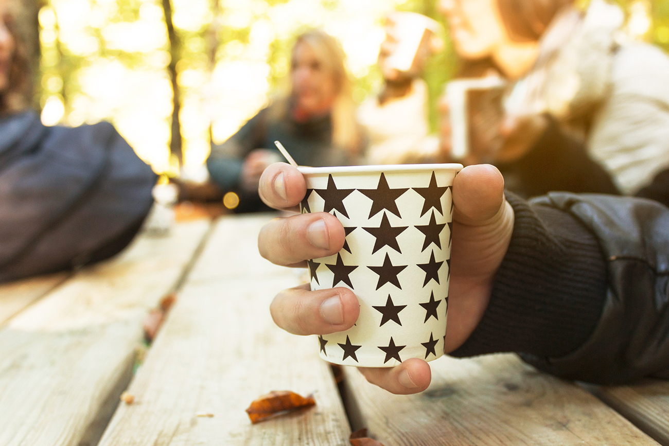 Kahvimukia pitelevä käsi, taustalla juttelevia ihmisiä.