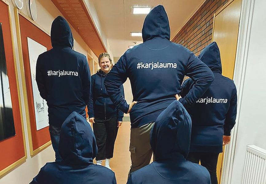 """Hupparipäisiä nuoria selin kuvattuna, hupparissa teksti """"karjalauma""""."""