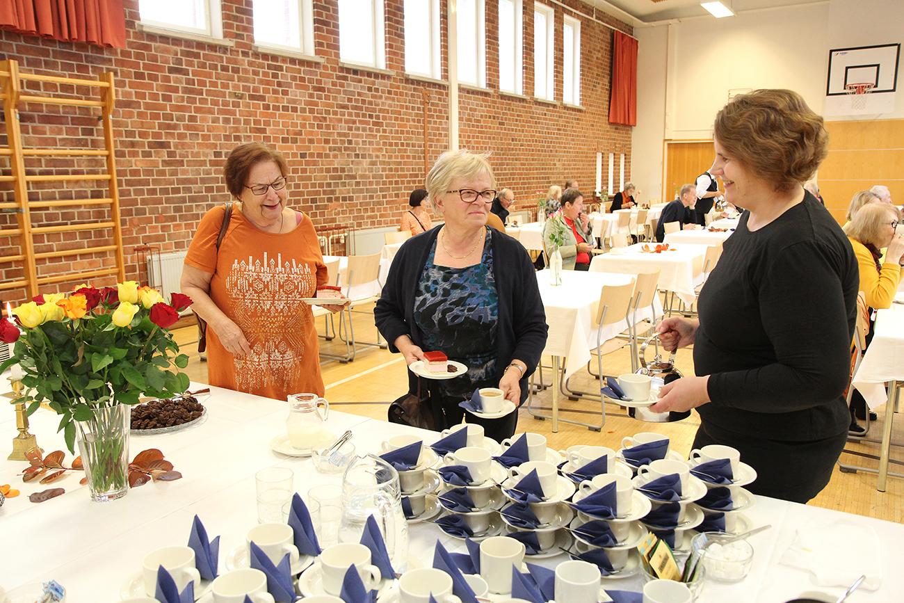 Seija Leskinen ja Hilkka Leskelä ottavat kahvia ja kakkua, joita Katja Vihelä tarjoilee.